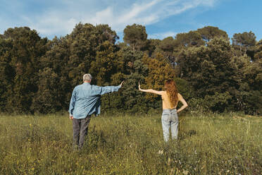 Rear view of woman and senior man with masks standing on meadow, safety distance - AFVF06601
