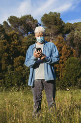 Senior man with mask using smartphone standing on meadow - AFVF06604