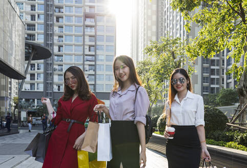 Female friends with shopping bags standing against buildings in city - JPTF00520