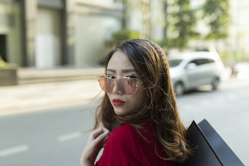 Close-up of confident woman wearing sunglasses carrying shopping bag on street in city - JPTF00532