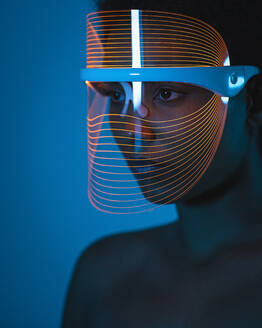 Close-up of woman wearing blue light therapy mask against wall at home - SNF00325