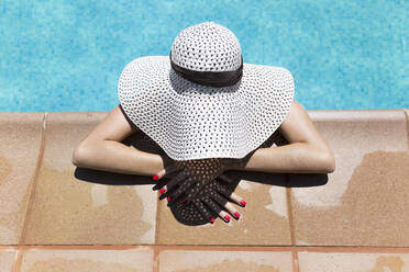 Young woman wearing hat relaxing at poolside during sunny day - JPTF00550