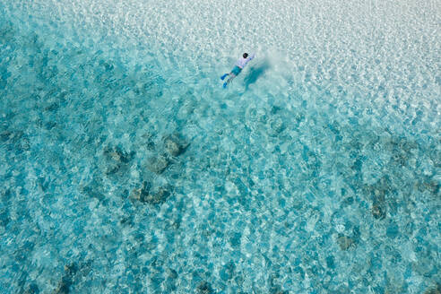 Aerial view of a man swimming on the shore of the beach with turquoise water in North Province, Maldives - AAEF08975