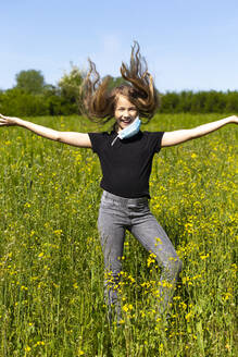 Cheerful girl with arms outstretched wearing mask dancing amidst plants against sky - JFEF00944
