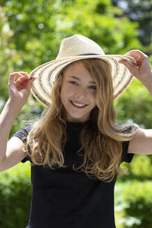 Close-up of smiling girl wearing hat while standing in park - JFEF00947