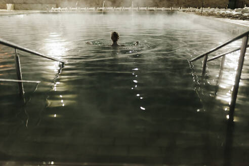 Mid adult woman swimming in hot pool at tourist resort during night - MRRF00080