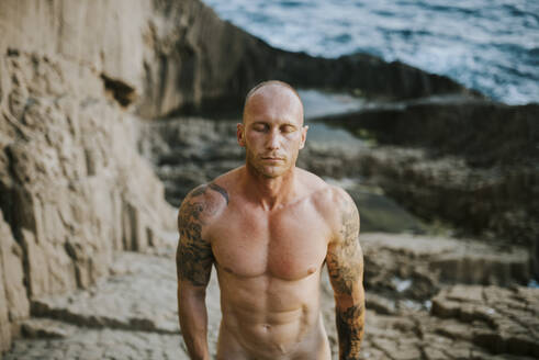 Tattooed nudist standing on volcanic rocks by the sea with closed eyes - MIMFF00051