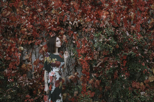 Thoughtful young woman standing against ivy wall during autumn in park - ALBF01304