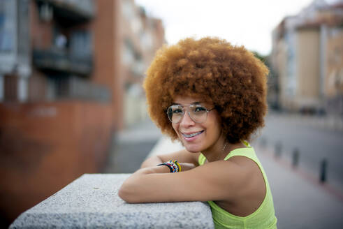 Close-up of smiling woman with afro hair standing by retaining wall in city - OCMF01352