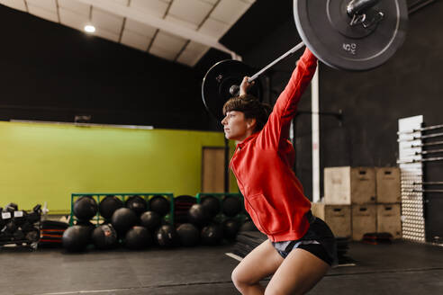 Female athlete lifting deadlift while standing in gym - MRRF00087