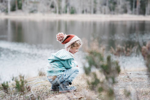 Young girl sitting on a rock smiling whilst hiking in Sweden - CAVF84972