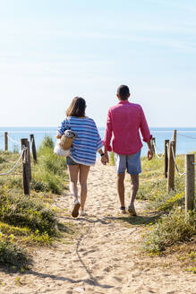 Back view of a young couple walking to beach while holding hands - CAVF84996
