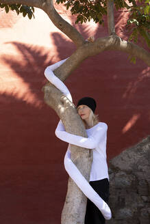 Thoughtful woman with artificial long hands embracing tree trunk against wall - PSTF00771