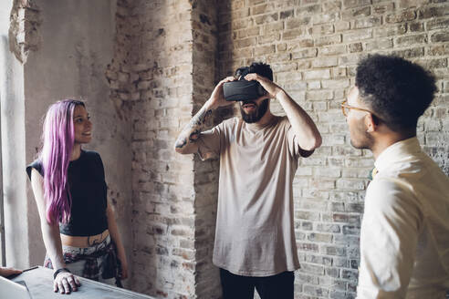 Creative team using Vr goggles in loft office - MEUF00721