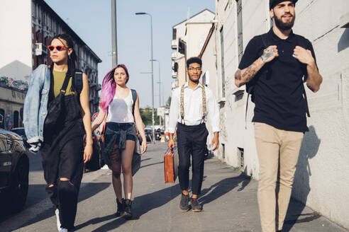 Group of friends walking on pavement in the city - MEUF00760