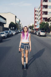 Portrait of a stylish young woman with pink hair standing on the street in the city - MEUF00775