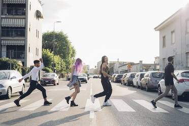 Group of friends crossing a street in the city - MEUF00784