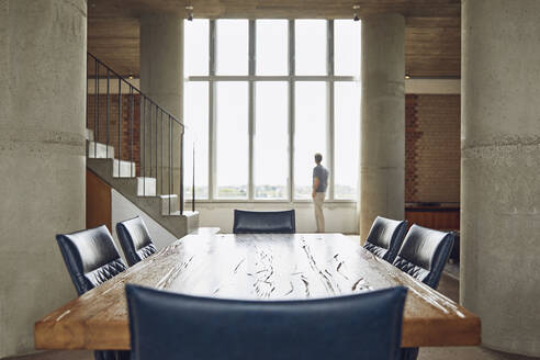 Wooden table in a loft flat with man at the window in background - MCF00932