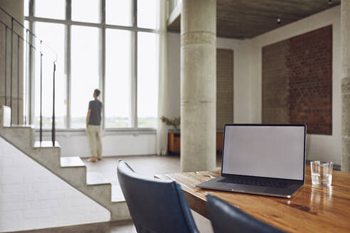 Laptop on wooden table in a loft flat with man at the window in background - MCF01025