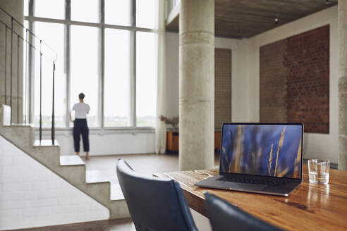 Laptop on wooden table in a loft flat with woman at the window in background - MCF01028