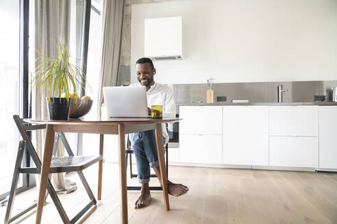 Portrait of smiling man sitting at table in modern apartment using laptop and earphones - AHSF02727