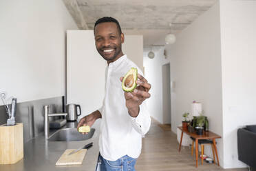 Portrait of smiling man with sliced avocado in his kitchen - AHSF02751
