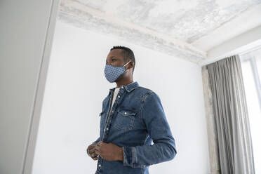 Man wearing reusable face mask indoors putting on his jeans jacket - AHSF02763