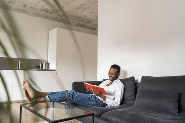 Smiling man sitting on couch in modern apartment reading a book - AHSF02766