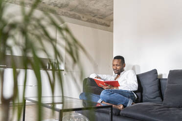 Portrait of man sitting on couch in modern apartment reading a book - AHSF02769