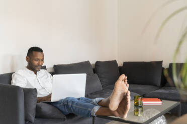 Portrait of man sitting on couch with feet up using laptop - AHSF02772