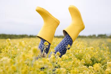 Girl's legs in yellow rubber boots in rape field - EYAF01128