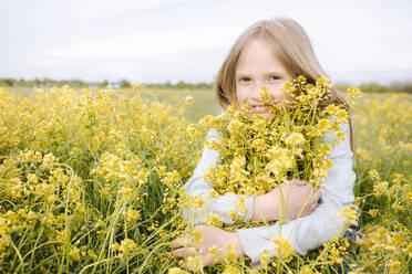 Smiling girl hugging rape flowers - EYAF01131