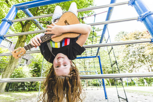Smiling girl hanging upside down on jungle gym while playing guitar at park - IHF00355