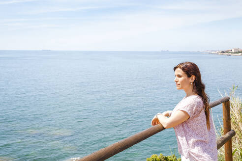Woman leaning on railing while looking at Ligurian Sea against sky during sunny day - FLMF00232