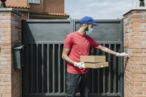Male delivery person using intercom while standing with package at house gate during coronavirus - XLGF00186