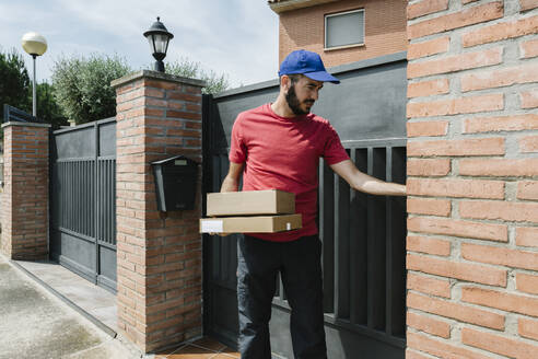 Bearded delivery person standing with packages against house gate on sunny day - XLGF00198
