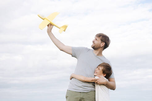 Happy boy embracing father holding toy airplane standing against sky - EYAF01148
