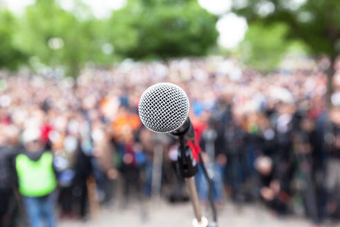 Close-Up Of Microphone Against Crowd In City - EYF05761