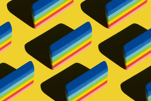 Pattern of rainbow colored erasers against yellow background - XLGF00202