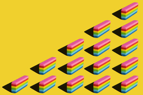 Pattern of rainbow colored erasers against yellow background - XLGF00205