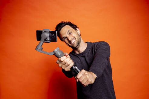 Cheerful man taking selfie while holding gimbal with smart phone against orange background - DAWF01599