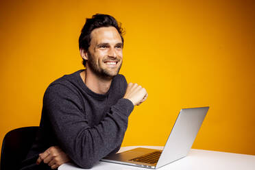 Thoughtful happy man looking away while sitting with laptop at table against yellow background - DAWF01620