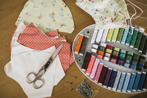Close-up of sewing items with floral protective masks on table at home - VBF00105