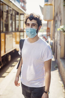 Young man wearing mask walking on city street during sunny day - MEUF00922