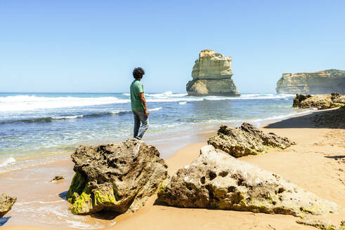 Man looking at sea against clear sky while standing on rock at Gibson beach, Great Ocean Road, Australia - KIJF03111