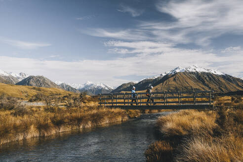 Couple of young hikers crossing a creek, Lake Clearwater, New Zealand - CAVF85401