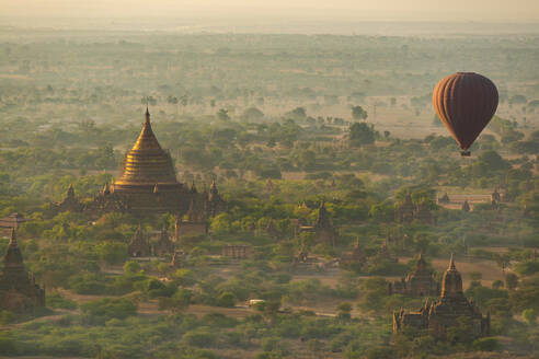 Myanmar, Mandalay Region, Bagan, Hot air balloon flying over Buddhist temples at dawn - TOVF00198