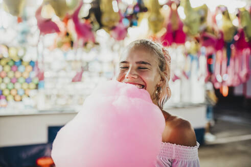 Close-up of smiling young woman with eyes closed holding cotton candy at amusement park - MIMFF00068