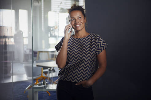 Portrait of smiling businesswoman on the phone in modern office - RBF07727