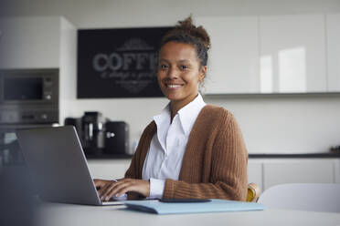 Portrait of smiling businesswoman working on laptop in kitchen - RBF07754